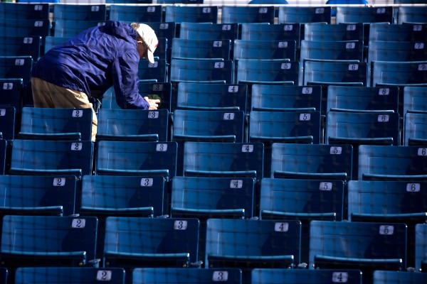 A workman wipes down the seats at Hadlock Field in Portland before Thursday's home opener against New Britain.
