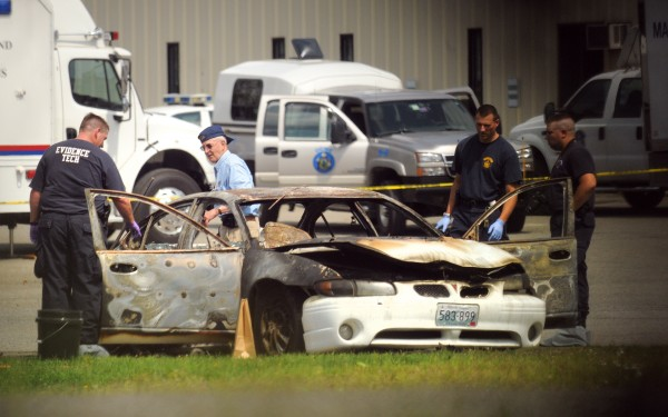 In this August 2012 file photo, Police check a vehicle that was found burning at Target Industrial Circle in Bangor. After the fire was extinguished, three bodies were discovered inside the car.
