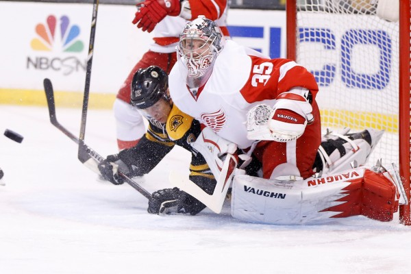 Detroit goaltender Jimmy Howard (35) maintains his concentration as he is crashed into by Boston's Jarome Inginla during Friday's NHL playoff game at TD Garden in Boston. Howard, a former University of Maine standout, helped the Red Wings shut out the Bruins 1-0.