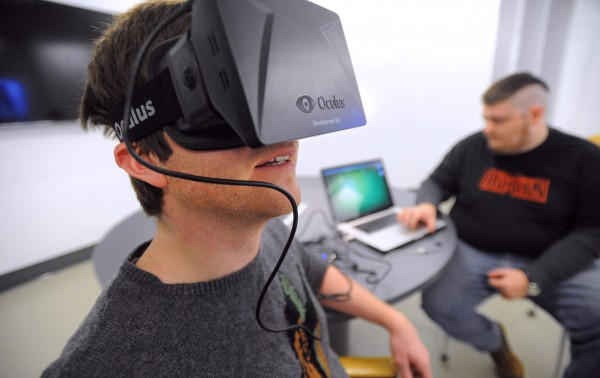 Lucas Richards (left) and Ian Lusk, new media majors at the University of Maine, use the new Oculus Rift virtual reality headset in their senior project Wednesday.