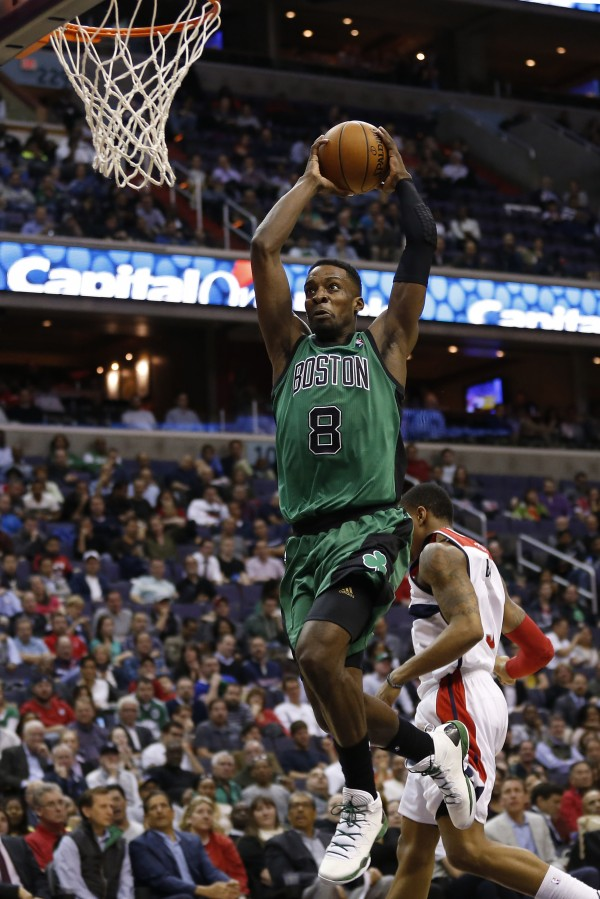 Boston Celtics forward Jeff Green dunks the ball past Washington Wizards guard Bradley Beal in the fourth quarter at Verizon Center in Washington Wednesday night. The Wizards won 118-92 and qualified for the NBA playoffs for the first time in seven seasons.