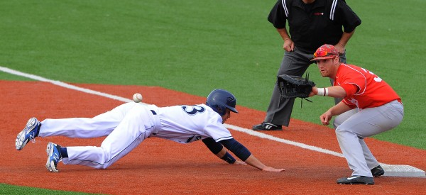 The University of Maine's Colin Gay (left) dives back to first base, beating the throw to the University of Hartford's Brady Sheetz, during the game at Mahaney Diamond in Orono on Monday afternoon.