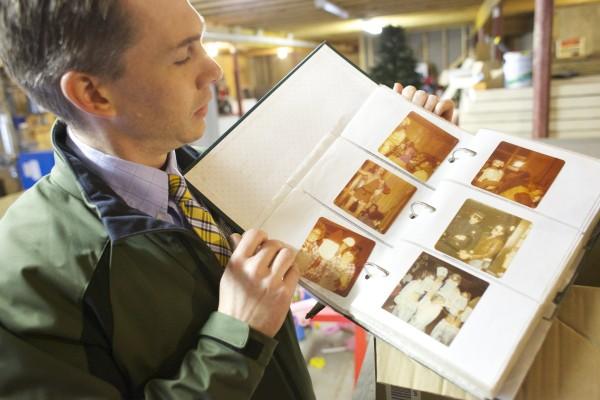 Dr. Orville Hartford holds up photo album from the Oronoka restaurant in Orono on Thursday.