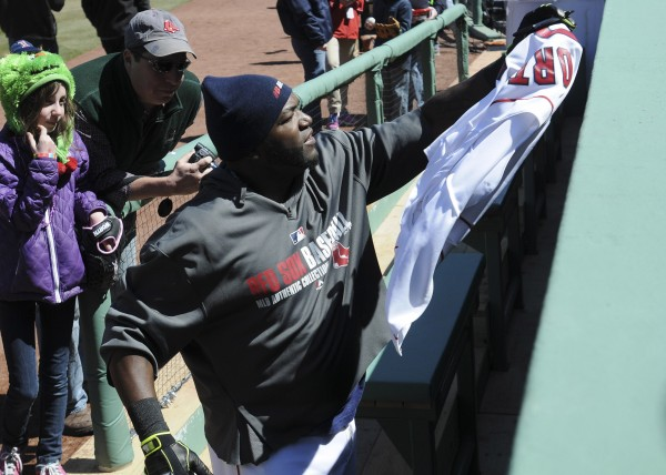 Boston Red Sox designated hitter David Ortiz (34) signs an autograph for a fan prior to a game against the Milwaukee Brewers at Fenway Park on Sunday.