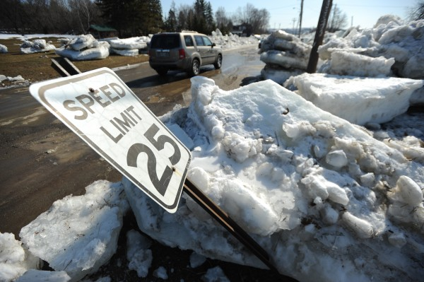 The speed limit sign along Riverside Avenue in Fort Fairfield lies on its side as curious motorists drive the street on Thursday looking at giant ice floes that have been cleared from the road after they overflowed the banks of the Aroostook River.