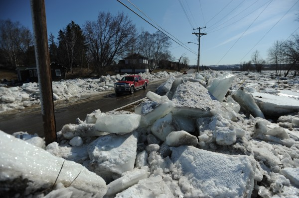 Motorists cruise Riverside Avenue in Fort Fairfield on Thursday looking at giant ice floes that have been cleared from the road after they overflowed the banks of the Aroostook River.