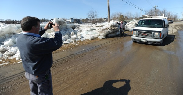Brian Bouchard takes a photo of co-worker Kevin Tompkins along Riverside Avenue in Fort Fairfield on Thursday. The two were looking at giant ice floes that have been cleared from the road after they overflowed the banks of the Aroostook River. Tompkins said he wanted the picture to show his kids.