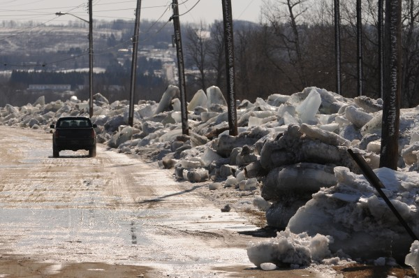 A motorist cruises Riverside Avenue in Fort Fairfield on Thursday looking at giant ice floes that have been cleared from the road after they overflowed the banks of the Aroostook River.