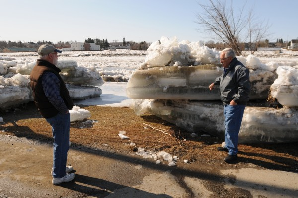 Bob Palm, left, and Stephen Lord inspect the giant ice floes along Riverside Avenue in Fort Fairfield on Thursday. The ice floes had been cleared from the road after they overflowed the banks of the Aroostook River.