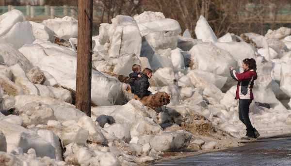 Erin Waskovich takes a picture of her sons, Duke and Wyatt, as they sit on the ice along Riverside Avenue in Fort Fairfield on Thursday. The three were looking at giant ice floes that have been cleared from the road after they overflowed the banks of the Aroostok River. &quotWho needs a jungle gym when you have these,&quot Waskovich said as her children climbed the ice.