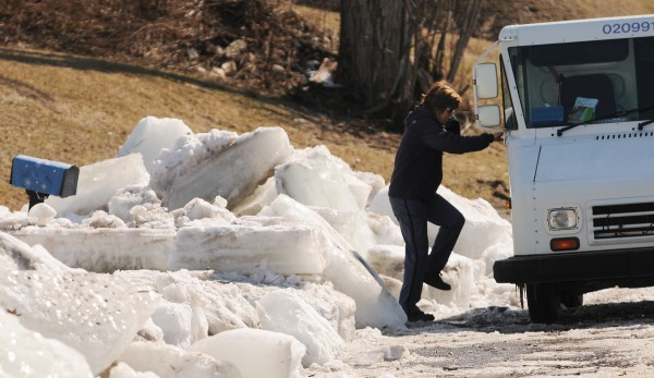 A postal worker retreats to her truck after delivering mail to an ice-bound mailbox on  Riverside Avenue in Fort Fairfield on Thursday. Giant ice floes have been cleared from the road after they overflowed the banks of the Aroostook River.