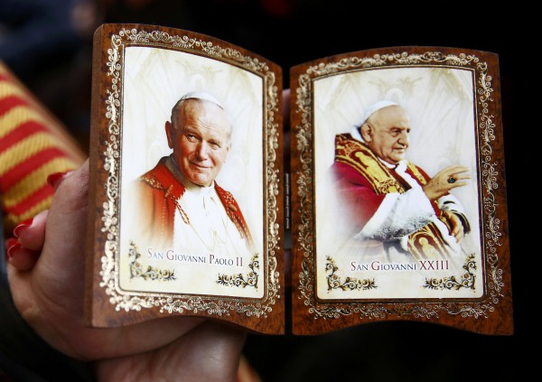 A Polish pilgrim displays a souvenir of canonised Popes John Paul II (left) and John XXIII while waiting for mass before the canonisation ceremony in St Peter's Square at the Vatican, April 27, 2014. Pope John XXIII, who reigned from 1958 to1963 and called the modernising Second Vatican Council, and Pope John Paul II, who reigned for nearly 27 years before his death in 2005 and whose trips around the world made him the most visible pope in history, were declared saints by Pope Francis at an unprecedented twin canonisation on Sunday.