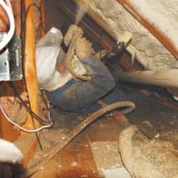 Skip Doodson of Circle D Sprayfoam maneuvers into some tight spaces to insulate an existing building with sprayfoam.