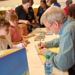 Young fans of Chris Van Dusen, Maine children's author and illustrator, watch as he signs their books.