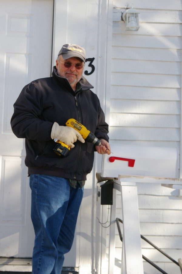 A volunteer with the EZ Fix program offered by the Eastern Area Agency on Aging moves from curbside to the front steps a mailbox for an elderly homeowner who encountered great difficulty in reaching the end of her driveway to get her mail. This simple project meant the woman could get her mail safely.