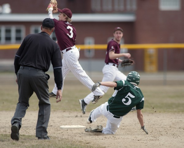Orono second baseman Dillon Cyr (3) leaps for a high throw on play at second base in the third inning of their game as Old Town player Kaleb Gifford (5) slides in safe in Orono, Maine, Tuesday, April 22, 2014.