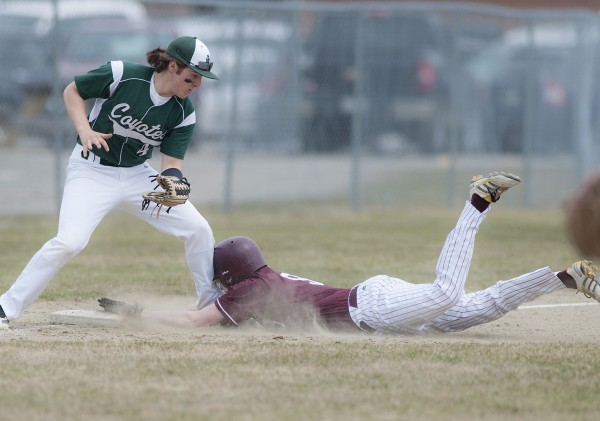 Orono player Ken Stokely (9) slides safely into third base under the glove of Old Town player Tyler Byther (4) on a steal in the second inning of their game in Orono, Maine, Tuesday, April 22, 2014.