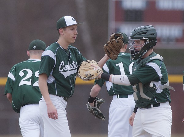 Old Town pitcher Garvey Melmed (7) , left, and catcher Tyler Young (13) encourage each other as the Coyotes take the field in the first inning of their game against Orono in Orono, Maine, Tuesday, April 22, 2014.