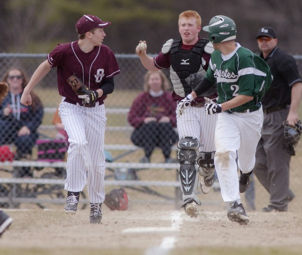 Orono catcher Jackson Coutts looks the runner, Old Town's Eric Hoogterp (22), back to third as Orono player Damien Heeger , left, looks for the ball in the top of the fifth inning of their game in Orono, Maine, Tuesday, April 22, 2014.