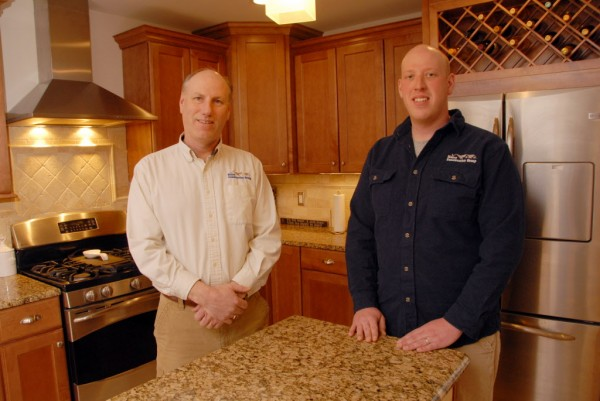 Standing in the center island kitchen located in an executive ranch built by Maine Construction Group are the company's partners, Ron Francis (left) and his son, Ryan Francis. The kitchen features Brazilian granite countertops, a GE Profile propane stove, a GE Profile refrigerator with French doors and a bottom freezer, a wine rack, under-cabinet LED lighting, and carmel maple cabinetry.