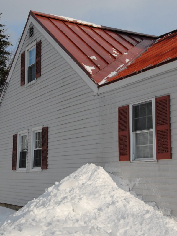 Snow removed from a metal roof lies piled beside a house in Hampden on New Year's Day 2014. Although pricey, metal roofing offers some advantages to traditional asphalt-shingle roofing; a metal roof tends to shed snow sooner, especially when temperatures warm toward 30 degrees, and last longer than a shingle roof.
