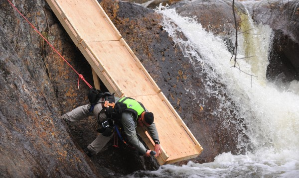 Aaron Bauman works on the launch ramp at the starting line of the Smalls to the Wall steep creek kayak race on the Sandy River in Township E Saturday, April 19. The ramp was used to bypass the first drop. Race organizer Andrew Cooper and safety coordinator Jeremy Cass thought it would have been dangerous to run that section it at that water level.