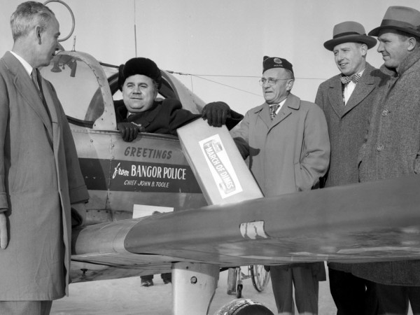 Richard Whittemore of Brewer, a victim of a paralyzing attack of polio in 1950, returned Tuesday from New York with a supply of miniature Blue Crutches which will be sold this weekend in most Eastern Maine communities to kick off the 1957 March of Dimes. Greeting Whittemore at the Old Town airport were left to right: James F. O'Connor of Bangor, chairman of Penobscot County chapter, NFIP; Whittemore; Arthur Littlefield of Bangor, chairman of the Penobscot County Blue Crutch drive; Donald Taverner of Orono, March of Dimes state chairman; and Robert E. Crabb of Bangor, Penobscot County March of Dimes director.