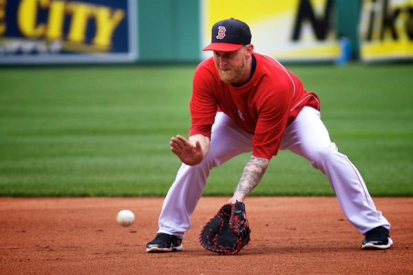 Red Sox infielder Mike Carp fields a ball at first base during batting practice at Fenway Park in Boston on Tuesday. Volunteers of America action teams from four Maine high schools were on hand to watch the Sox beat the Tampa Bay Rays 7-4.