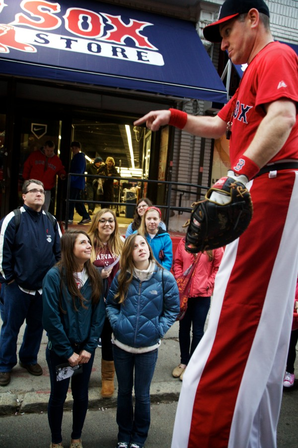 A man on stilts, who goes by the name &quotBig League Brian,&quot jokes with students from York High School on Yawkey Way in Boston on Tuesday before a Red Sox game. The students, all Volunteers of America action team members, were treated to the game by Moody's Collision Center and the Major League Baseball Players Trust.