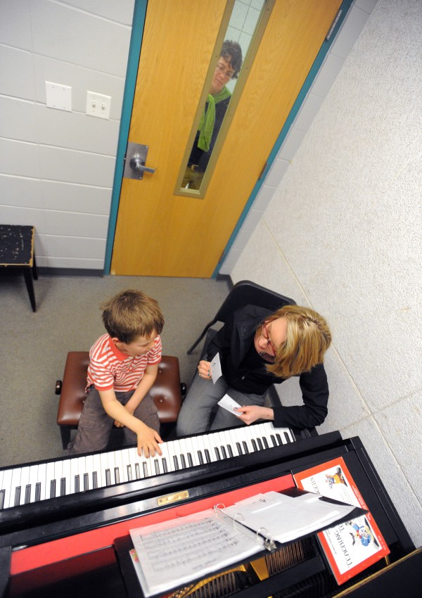 Sierra Ventura works with piano student Liam Waring, 6, at the University of Maine in Orono on Thursday. Liam started taking lessons from Ventura in the fall of 2013 and is one of her 35 students. Peeking through the window is Liam's mother, Katie Quirk.