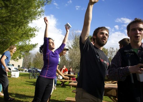 Rebecca Zerlin (from left), Caleb Roebuck and Jake McGinley cheer winning the Epic Failure Award after racing their cardboard kayak in the second annual Unity College Cardboard Kayak Race at Unity College on Friday.