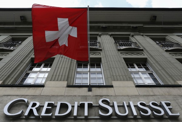 The logo of Swiss bank Credit Suisse is seen below the Swiss flag at a building in the Federal Square in Bern May 15, 2014.