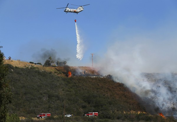 A U.S. military helicopter drops water on a burning hillside as it helps fight the Cocos Fire in San Marcos, California  May 15, 2014.