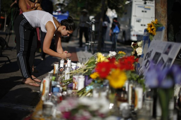 A woman lights a candle at a makeshift memorial for 20-year-old UCSB student Christopher Michael-Martinez outside a deli that was one of nine crime scenes after series of drive-by shootings that left 7 people dead in the Isla Vista neighborhood of Santa Barbara, California May 25, 2014.
