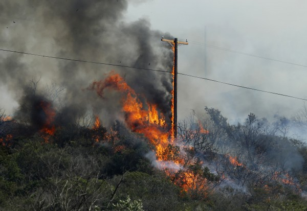 A power line goes up in flames along a hillside as the Cocos Fire continues to burn in San Marcos, California  May 15, 2014.
