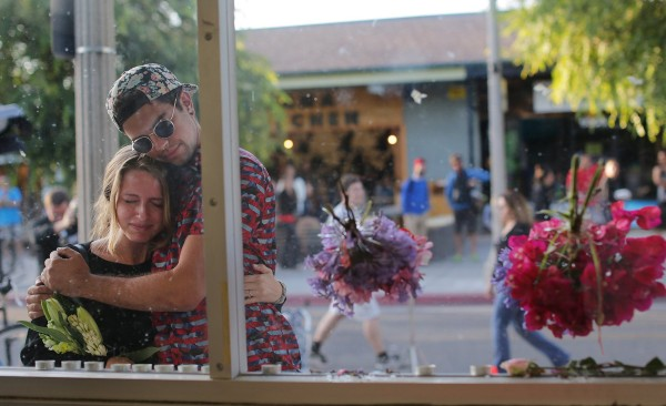 University of California Santa Barbara student Connor London gets a hug from fellow student Noel Peake after placing fresh flowers at a memorial for victims of Friday's shooting rampage at the I.V. Deli Mart on May 25, 2014, in Isla Vista, Calif.