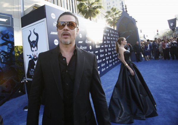 Actor Brad Pitt waits as cast member Angelina Jolie poses, at the premiere of &quotMaleficent&quot at El Capitan theatre in Hollywood, California May 28, 2014.