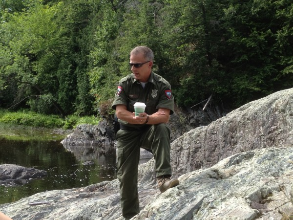 Maine game warden Jim Fahey surveys the Kenduskeag Stream in Bangor during the summer of 2012, when a lone Atlantic salmon swam back and forth in a pool for several days. Fahey is back on the Kenduskeag regularly this spring, telling anglers that they can't keep any salmon that they might catch incidentally.