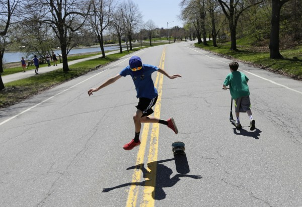 Nick Weiner attempts a trick on his skateboard while a friend rides by on a scooter in the middle of Baxter Boulevard.