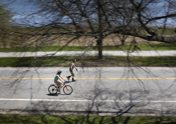 A bicyclist and an in-line skater travel down Baxter Boulevard.
