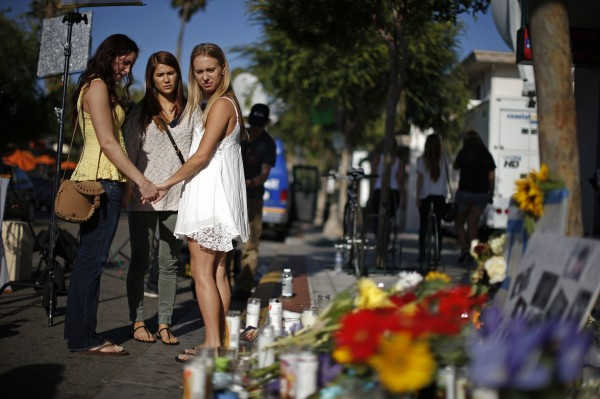 Amber McCoy, 20 (left), Ava Ames, 23, and Jenn Bowman, 21, pray in front of a makeshift memorial for 20-year-old UCSB student Christopher Michael-Martinez outside a deli that was one of nine crime scenes after series of drive-by shootings that left 7 people dead in the Isla Vista neighborhood of Santa Barbara, California May 25, 2014.