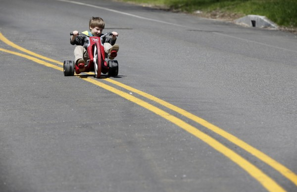 Noah Jordan, 4, rides his Radio Flyer down the center of Baxter Boulevard on the morning of May 11, shortly after the road was closed to automobile traffic for the day.