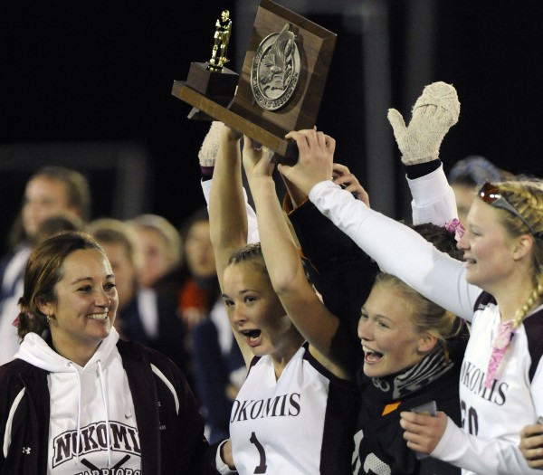 Nokomis coach Katie Thompson, left, and team seniors  Jordin McGinnis (1), Maria Adams (42) and teammate Ali Manson (20) with the State Championship trophy after defeating York Saturday, Oct. 30, 2010.