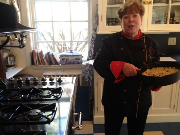 Chef Nancy Cerny of The CVC Catering Group shows off her skillet chocolate chip cookies by a Heartland stove.