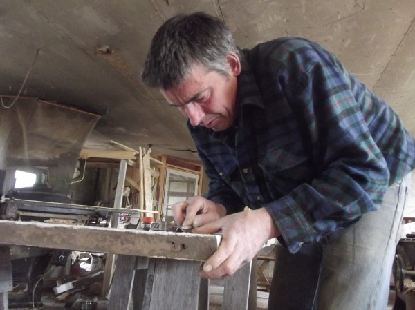 Erik Squire works at restoring an original door of the Whiting Union Meeting House at his shop in Machias on Saturday.