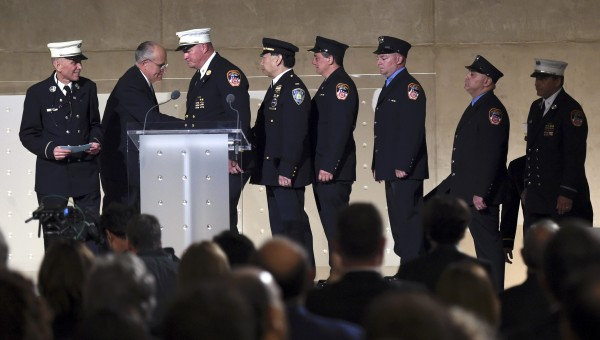 Former New York City Mayor Rudolph Giuliani (second left) shakes hands with firefighters and police officers at the dedication of the National September 11 Memorial & Museum on Thursday in New York.