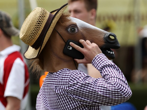 A fan in a horse mask talks on his cell phone before the 139th Preakness Stakes at Pimlico Race Course.