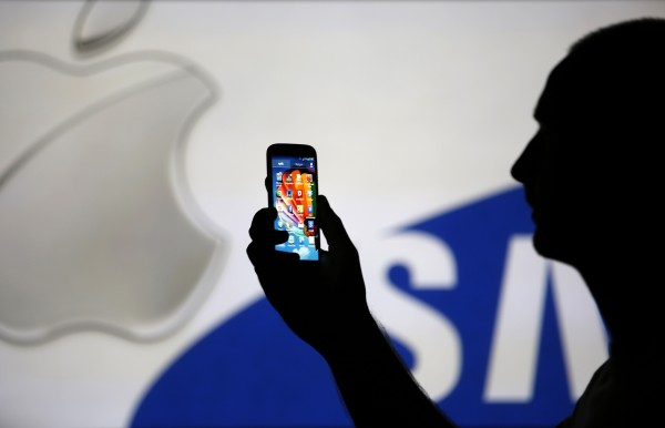 A man is silhouetted against a video screen with Apple and Samsung logos as he poses with a Samsung S4 smartphone in the central Bosnian town of Zenica, in this August 2013 file photo illustration. A U.S. jury on Friday ordered Samsung Electronics to pay $119.6 million to Apple Inc., after it found the South Korean smartphone maker had infringed two Apple patents.