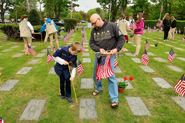 Cub Scout Asher Stephenson, Augusta, and his father Scott were among the many volunteers at the flag project Saturday morning at the Maine Veterans Memorial Cemetery in Augusta.