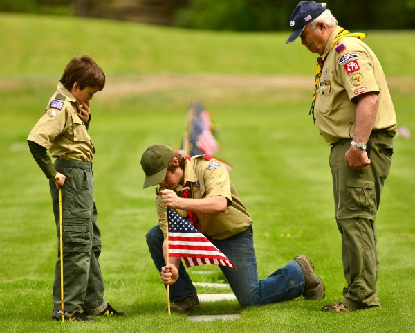 Boy Scout Michael Embry, center, plants a flag with the help of fellow scout Hunter Praul, left, and scout leader, Ronald Emery, who served with the Maine Air National Guard in Bangor for 25 years and retired as a master sergeant.